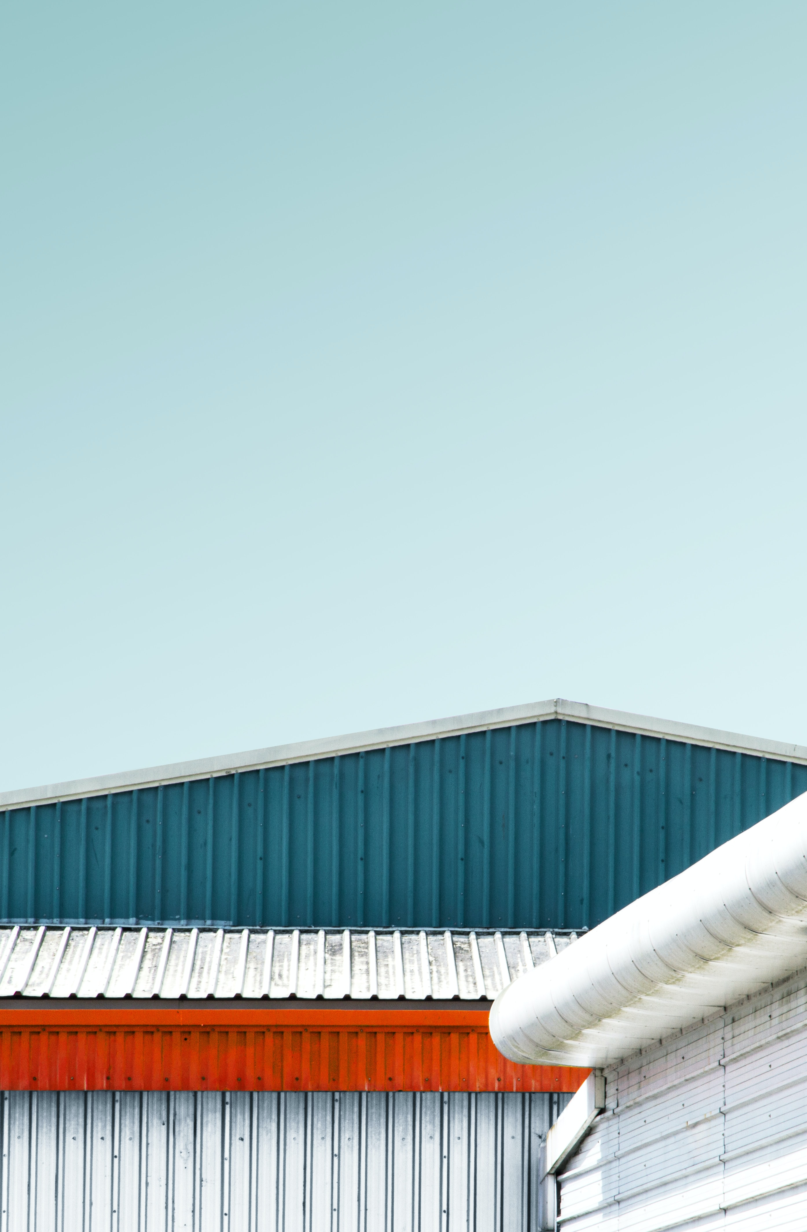 photo of gray and teal metal warehouse under clear sky