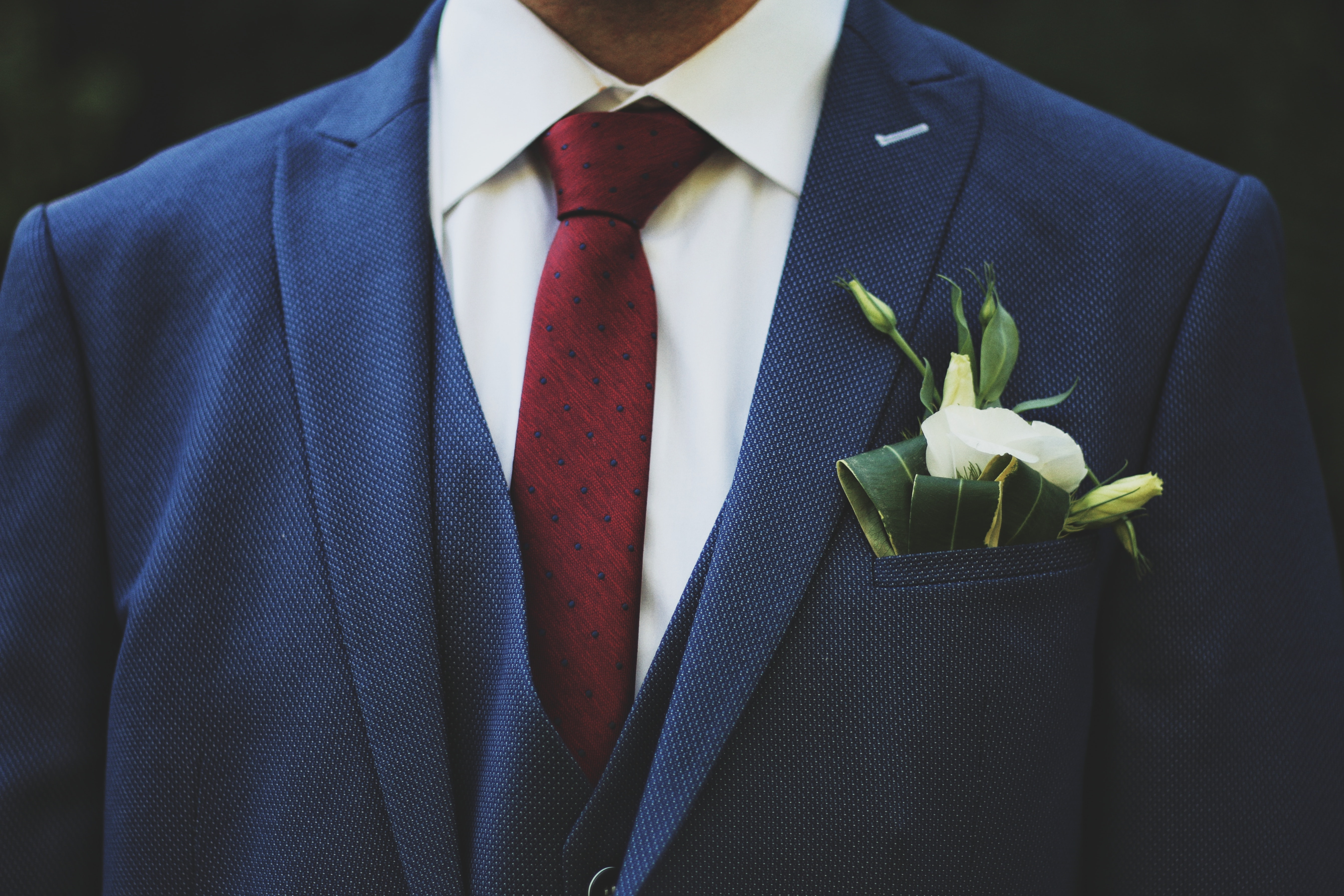 person wearing blue suit jacket and red necktie