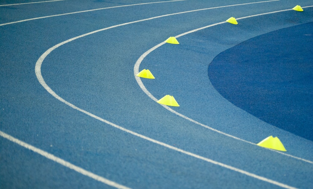 blue curved track field at daytime