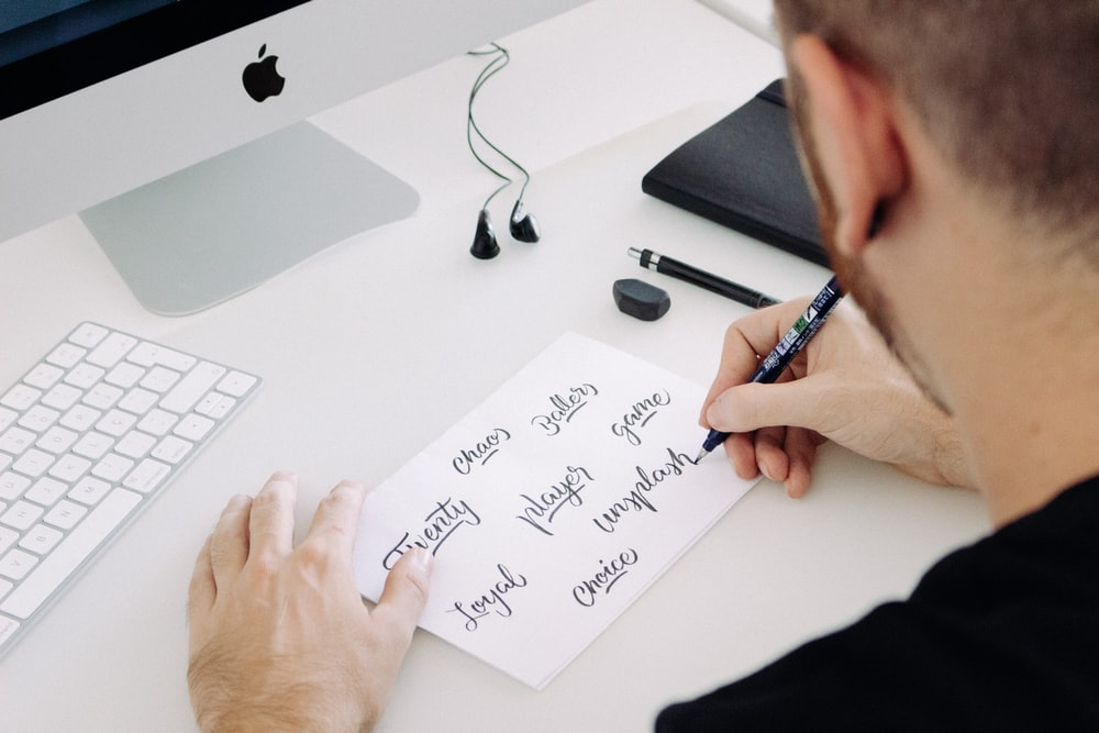 person writing on white printer paper in front of silver iMac