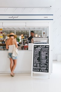 woman with white spaghetti strap top near the bar