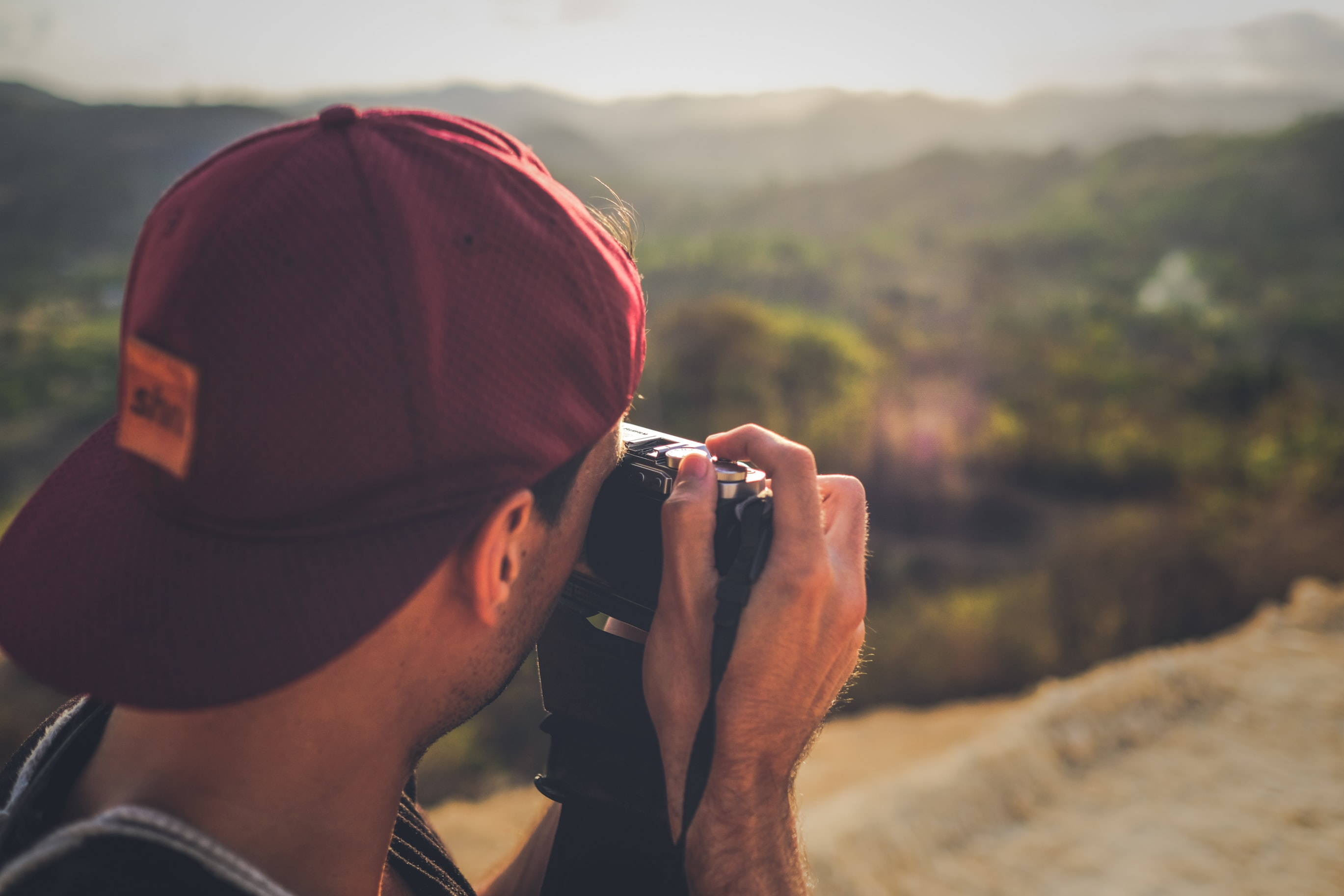 man in red fitted cap taking picture