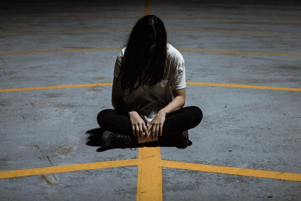 closeup photo of woman sitting on concrete pavement