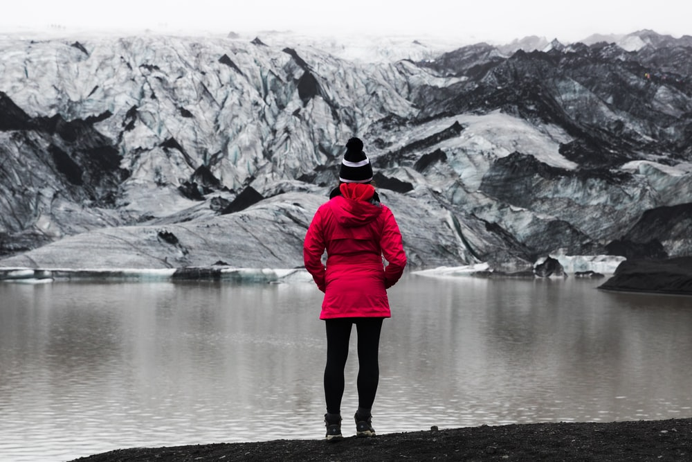 woman standing in front of mountain covered with snow