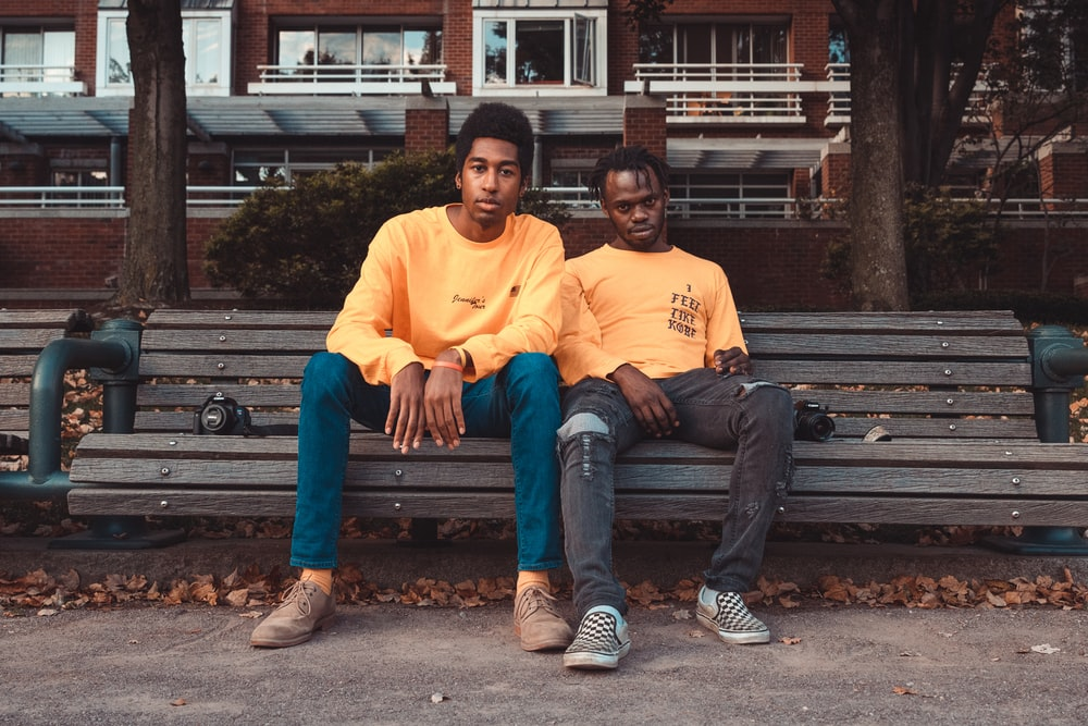 two men's sitting on brown wooden bench chair
