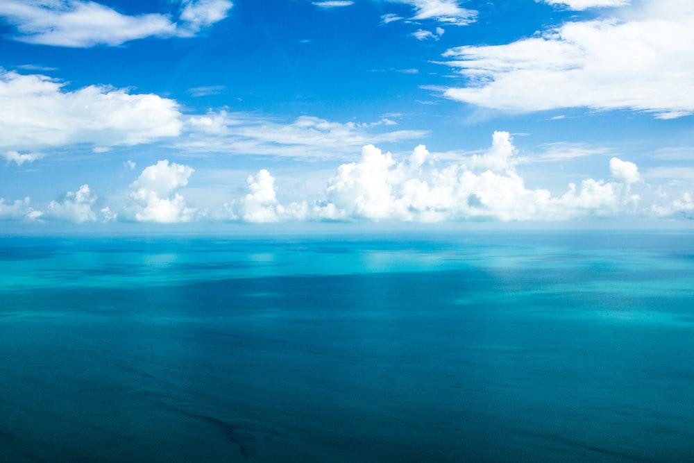 blue ocean under blue cloudy skies
