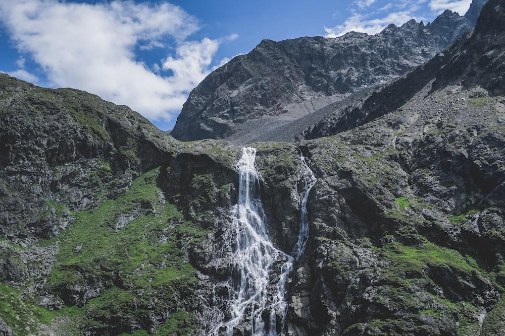 waterfalls near mountains during daytime