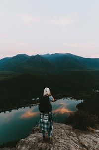 woman standing on cliff taking picture of mountain