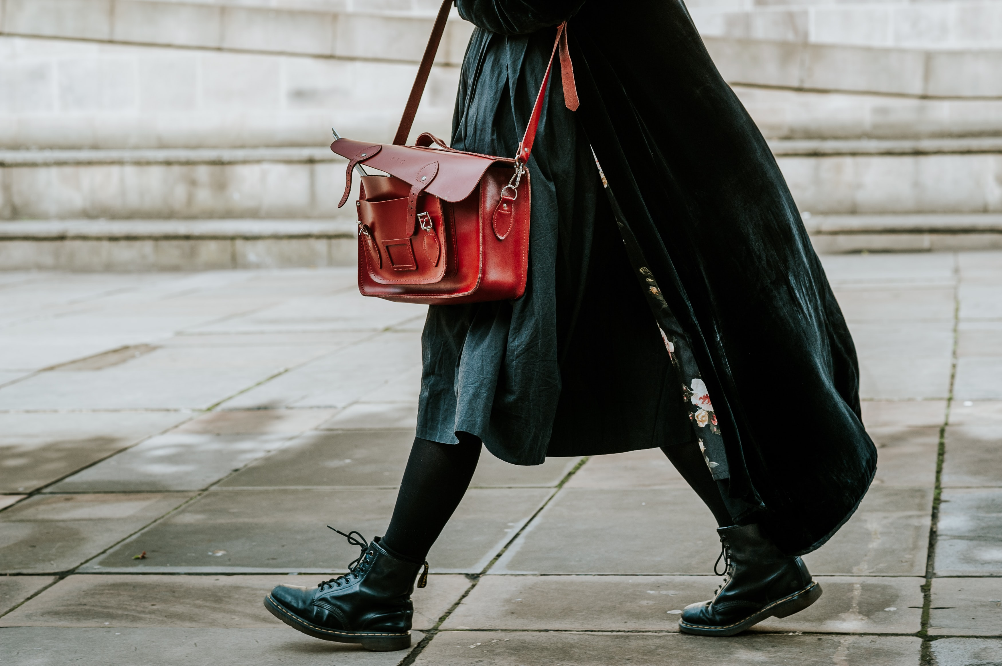 person in black coat carrying satchel bag while walking on street