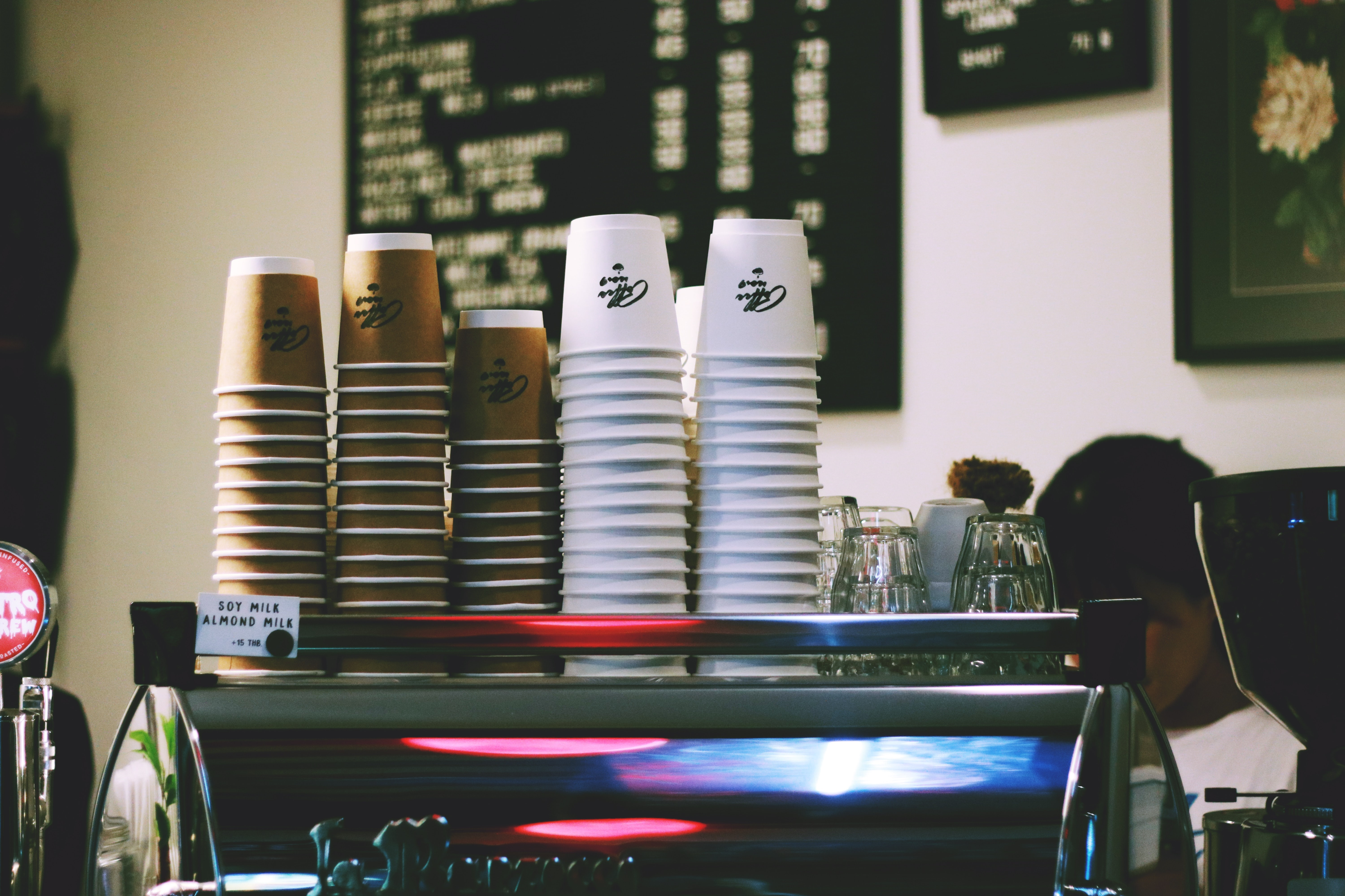 stacked of white and brown disposable cups on espresso maker