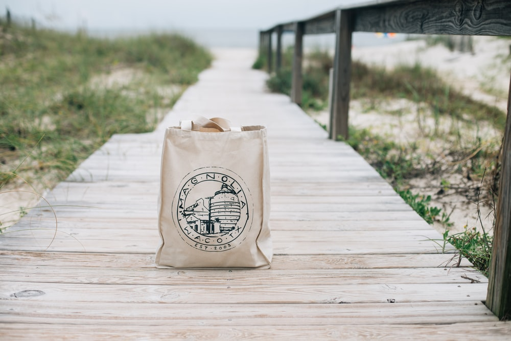 beige fabric shoulder bag on brown wooden pathway during daytime
