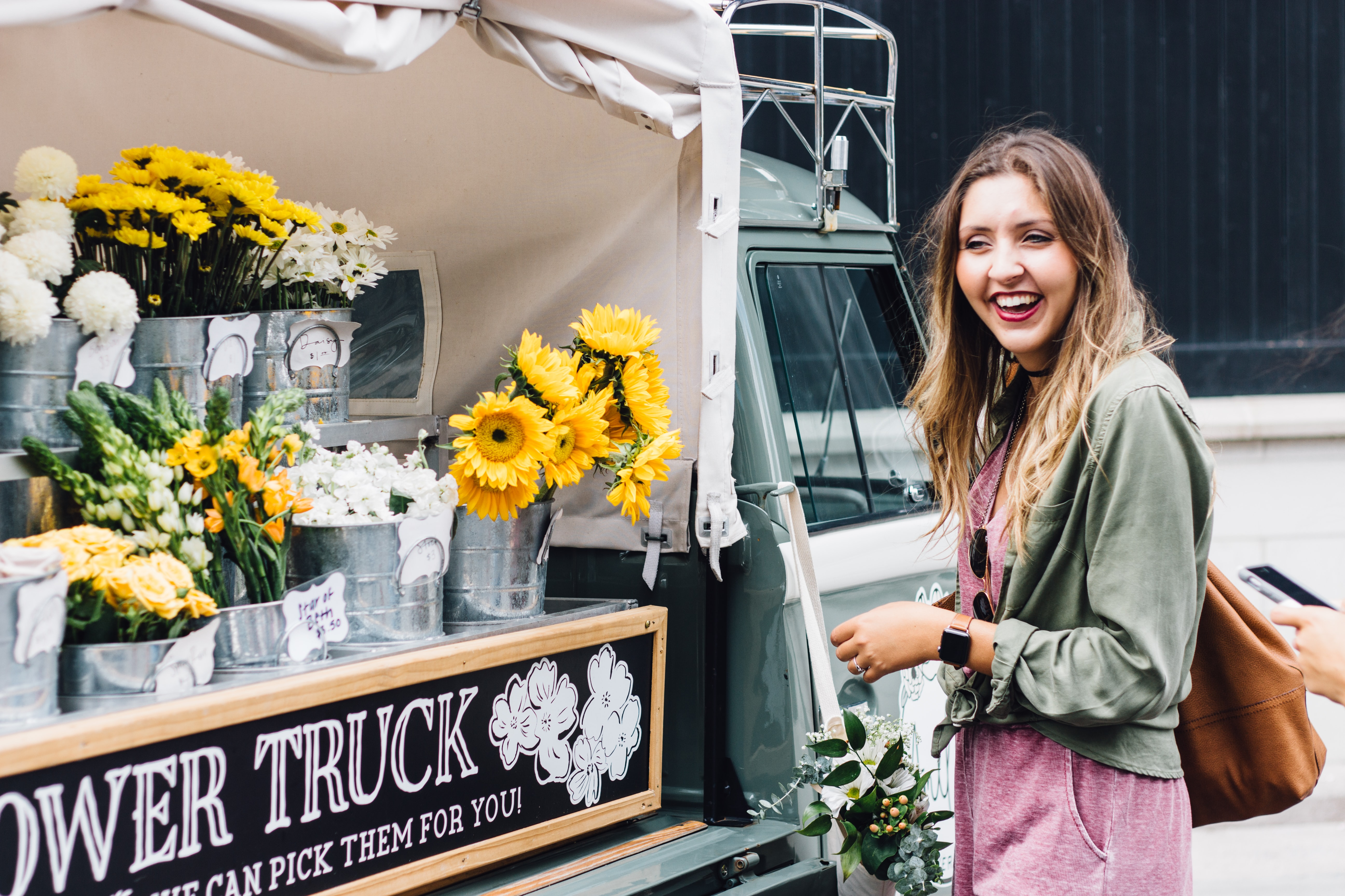 woman laughing in font of flower truck