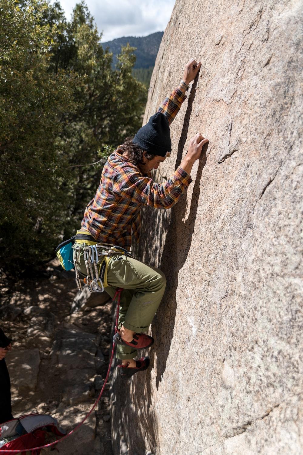 man climbing on rock during daytime