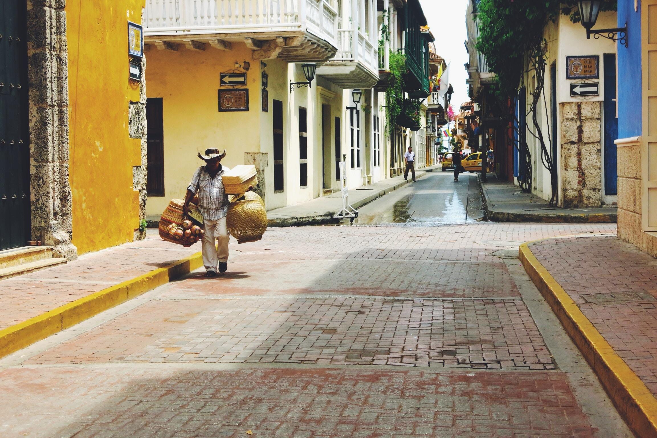 man selling baskets walking on street between buildings