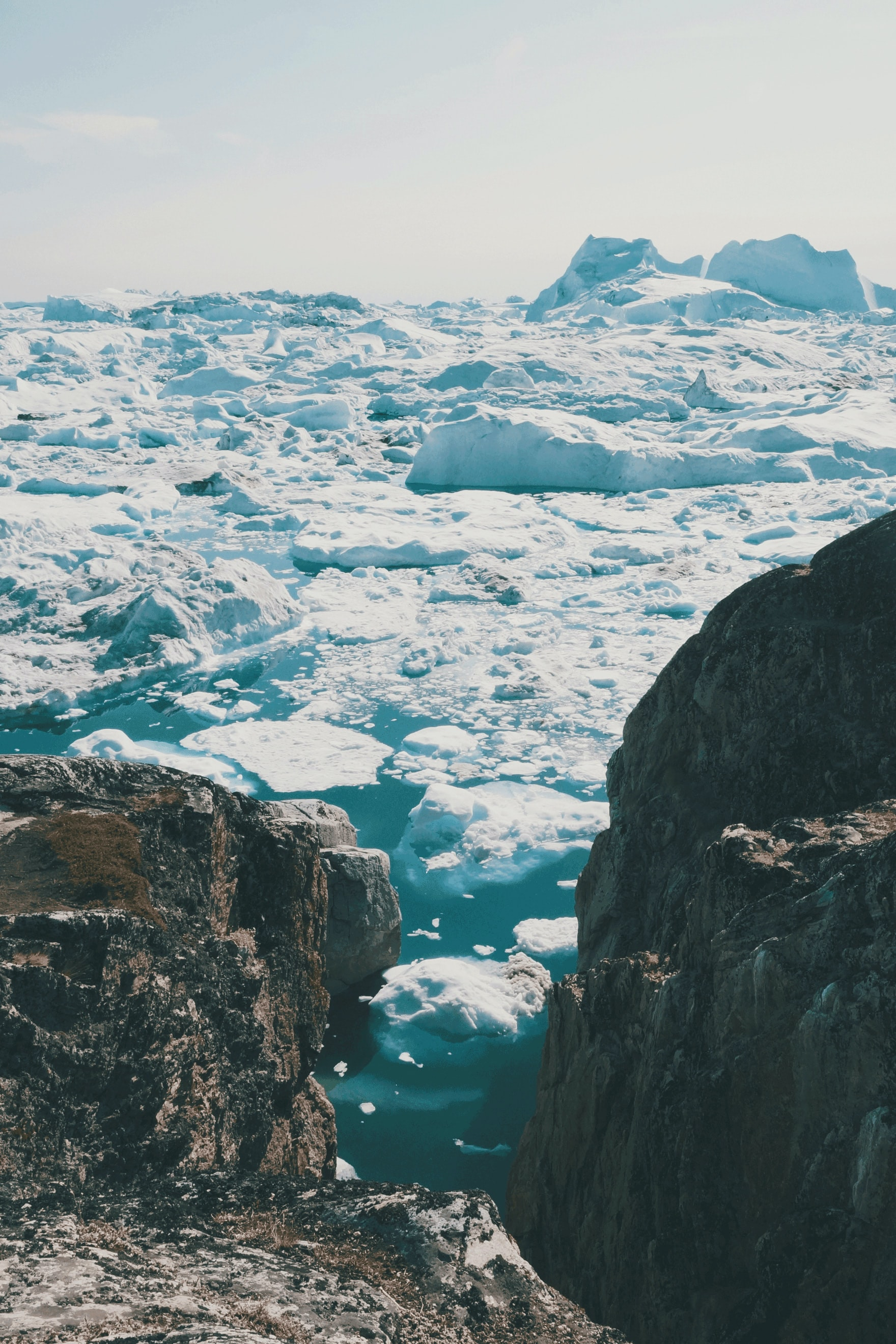 two brown rocks surrounded by ice blocks under white sky during daytime