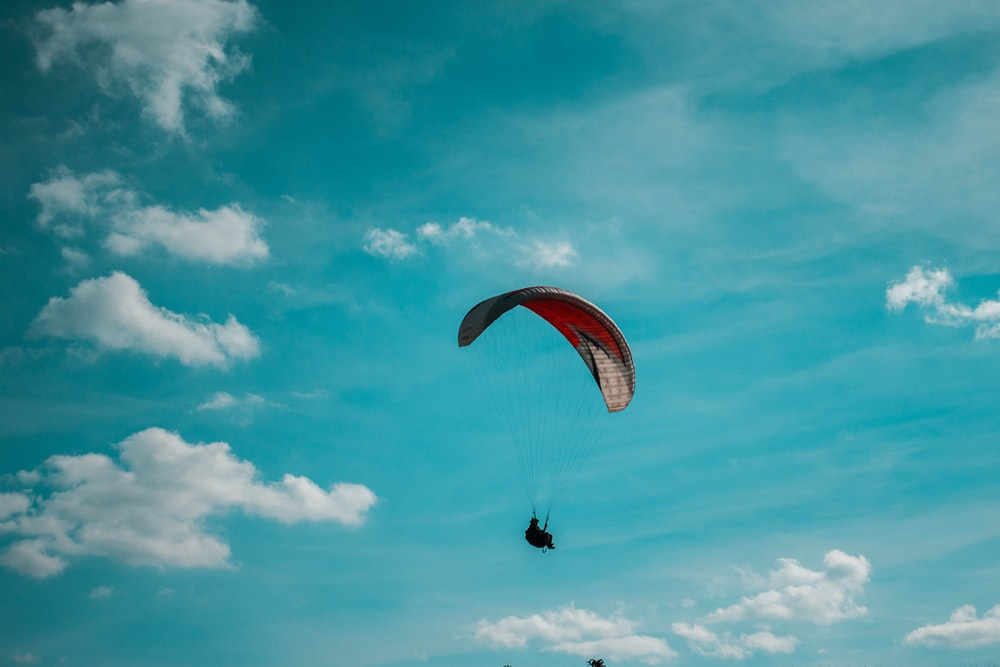 person riding parachute during daytime