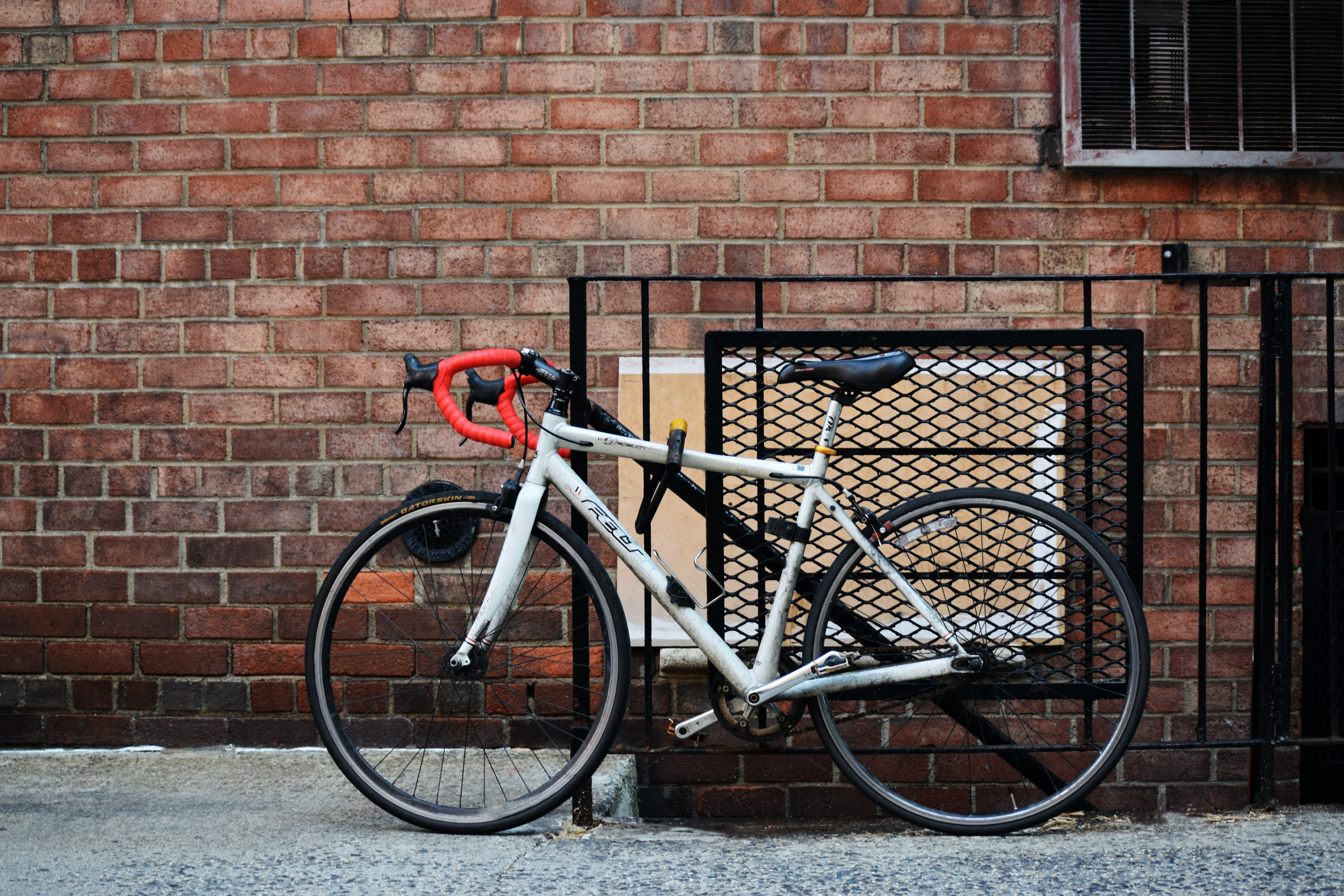 white road bike parked beside the gate