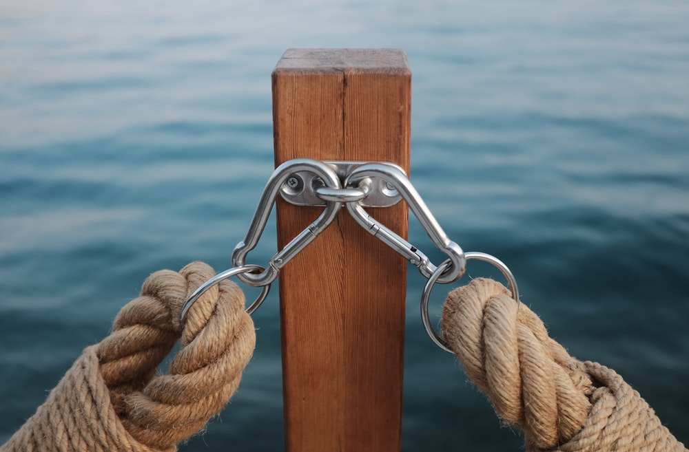 two rope with carbiner hooked on brown wooden post