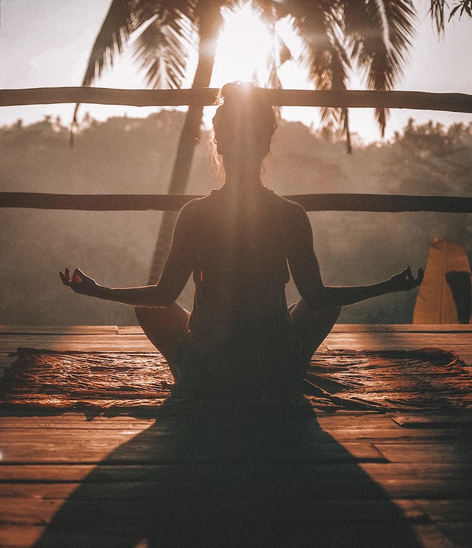 茶色の寄木細工の床でヨガ瞑想をしている女性