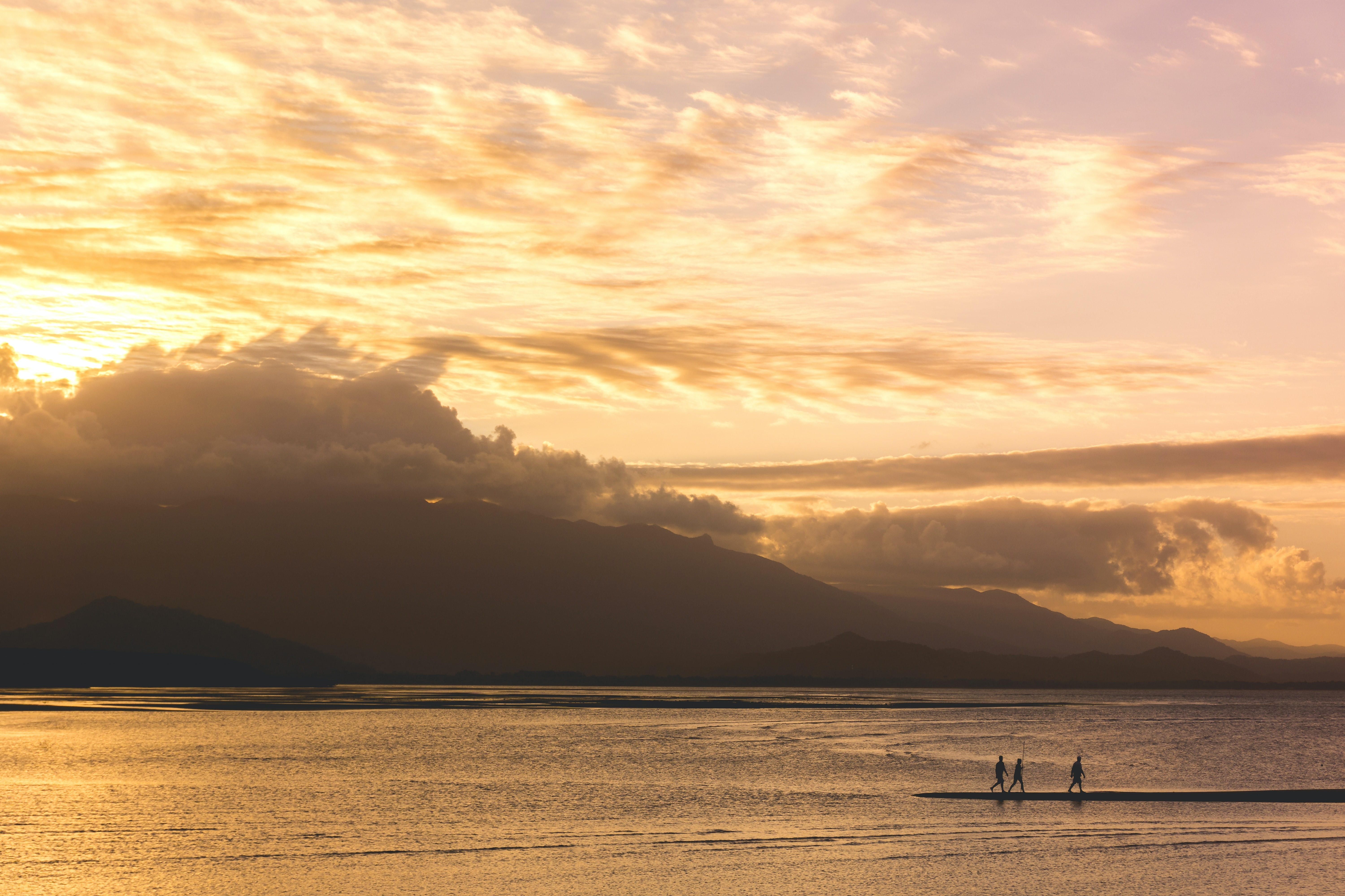 silhouette of three people walking on body of water during golden hour