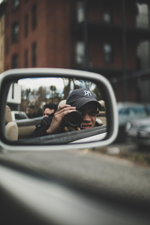 reflection of man taking a photo using DSLR camera