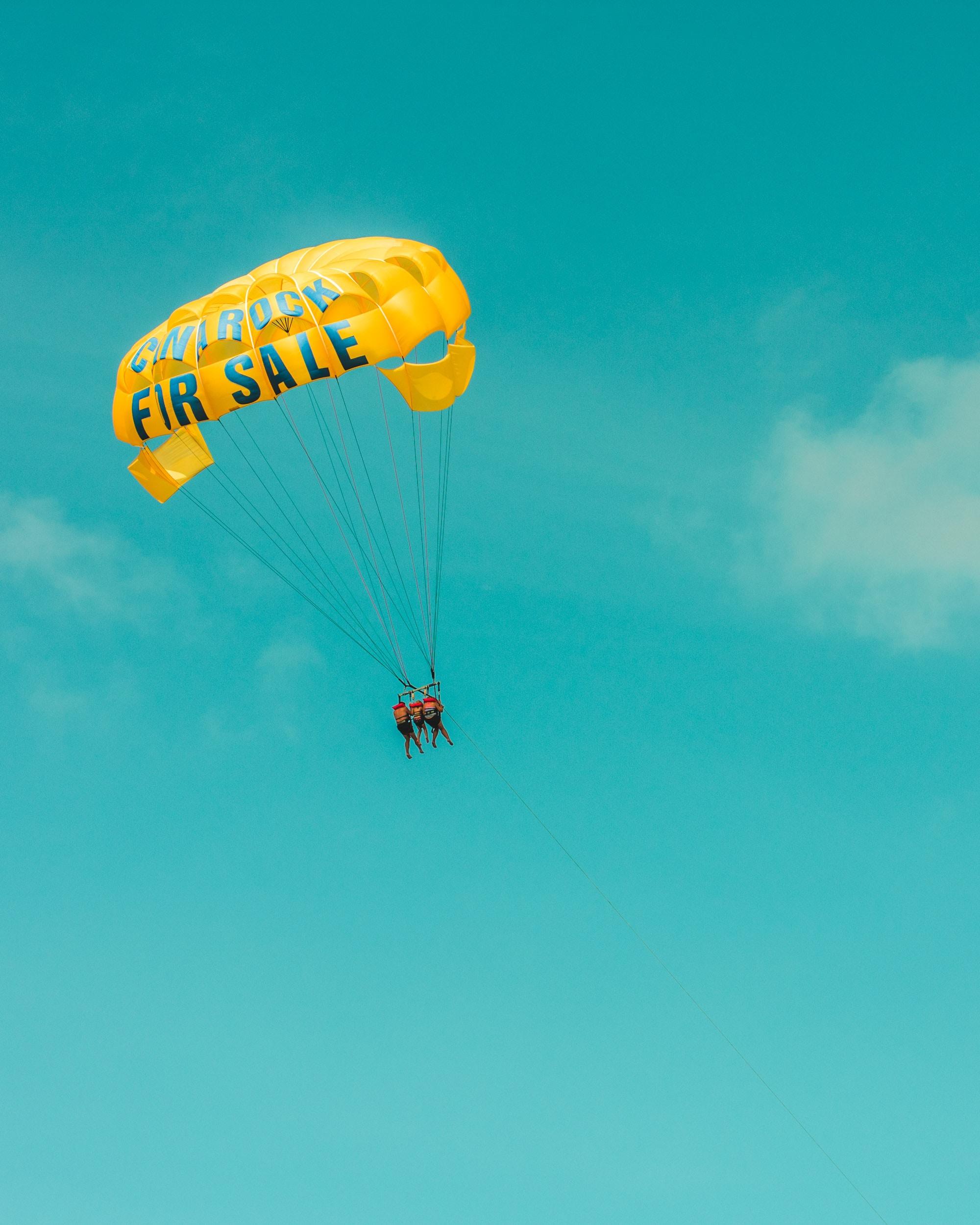 three person on yellow parachute
