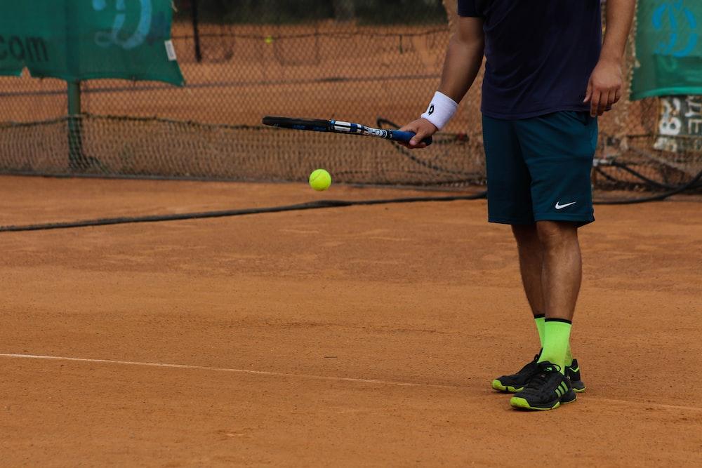 man in blue Nike shorts playing tennis