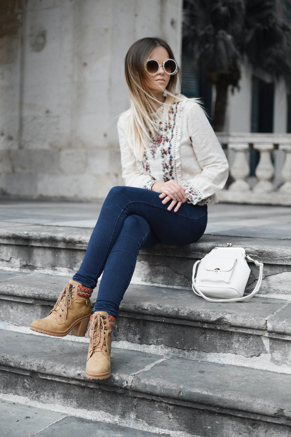 woman sitting on gray concrete stair