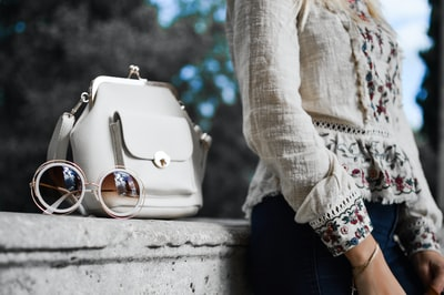 woman wearing beige and red floral top leaning on gray concrete slab with white leather bag ontop fashion zoom background