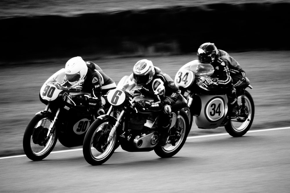grey scale photo of motorcycle racing in action