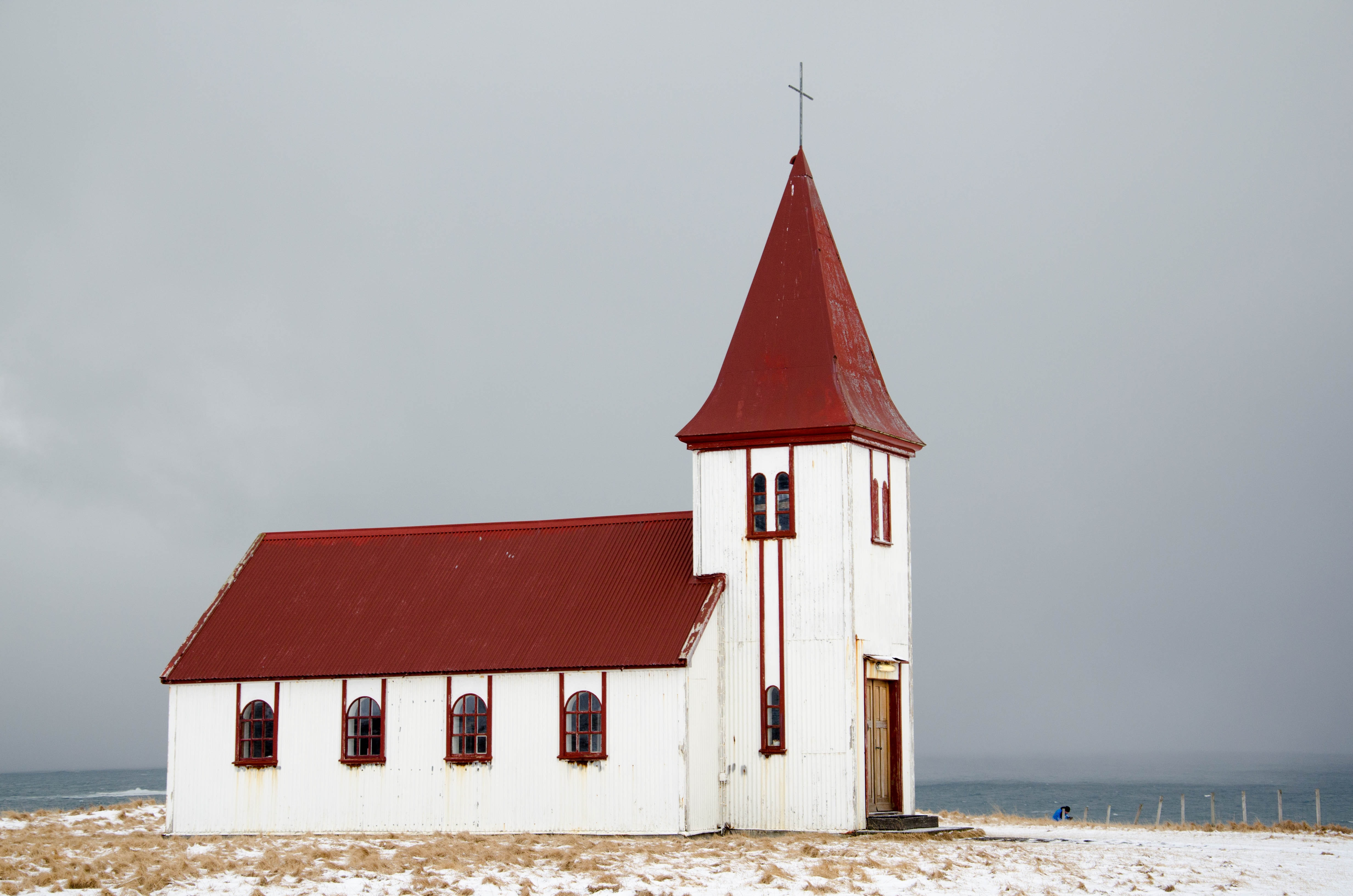 chapel near ocean under grey clouds
