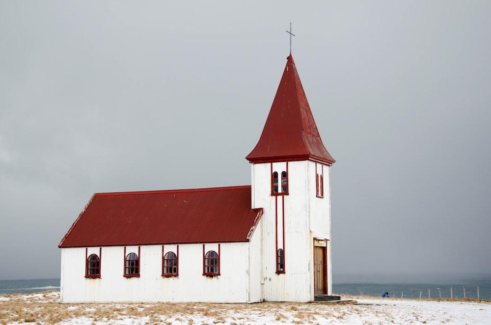 chapel near ocean under grey clouds