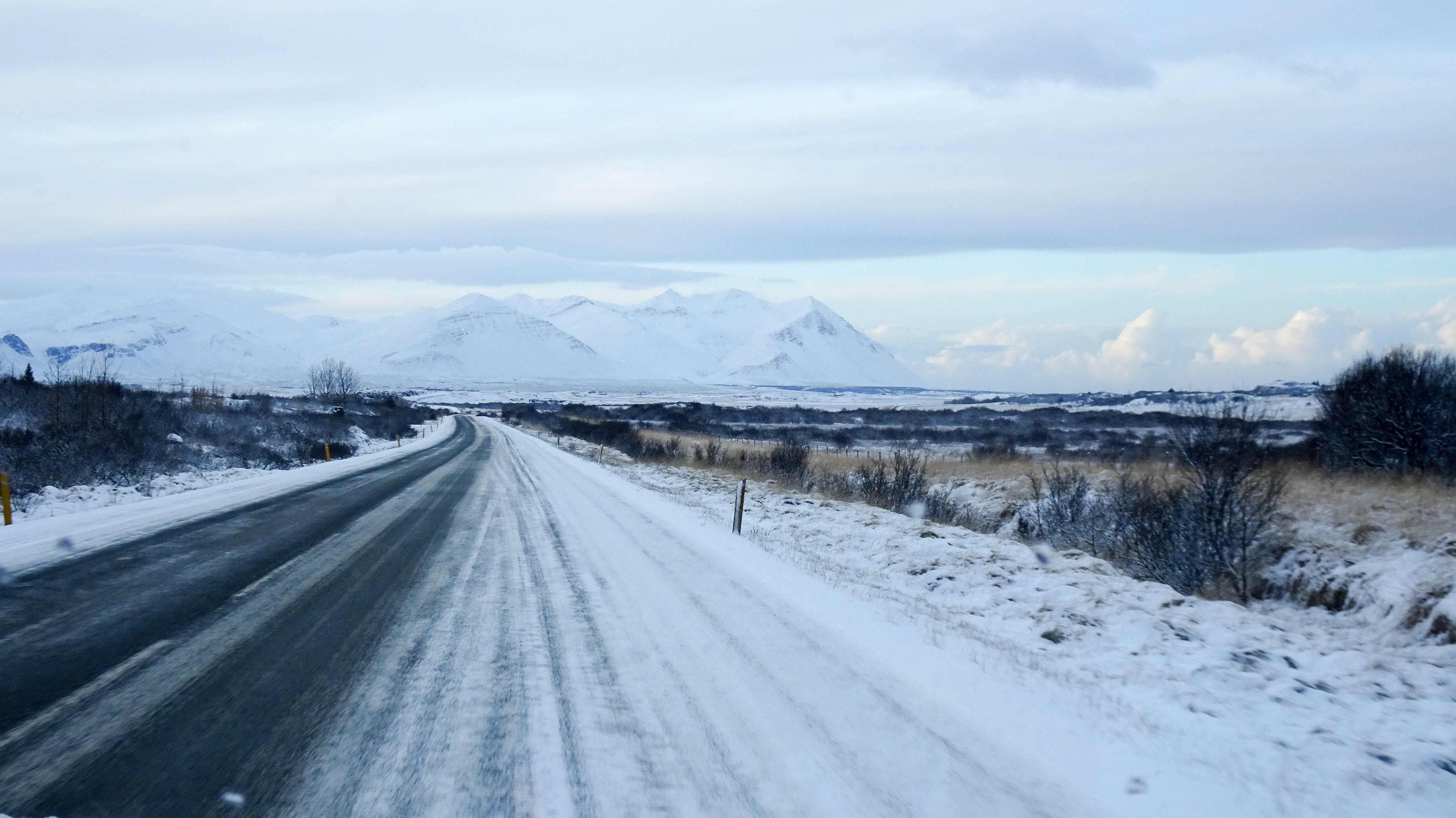 asphalt road covered with snow under white cloudy sky at daytime