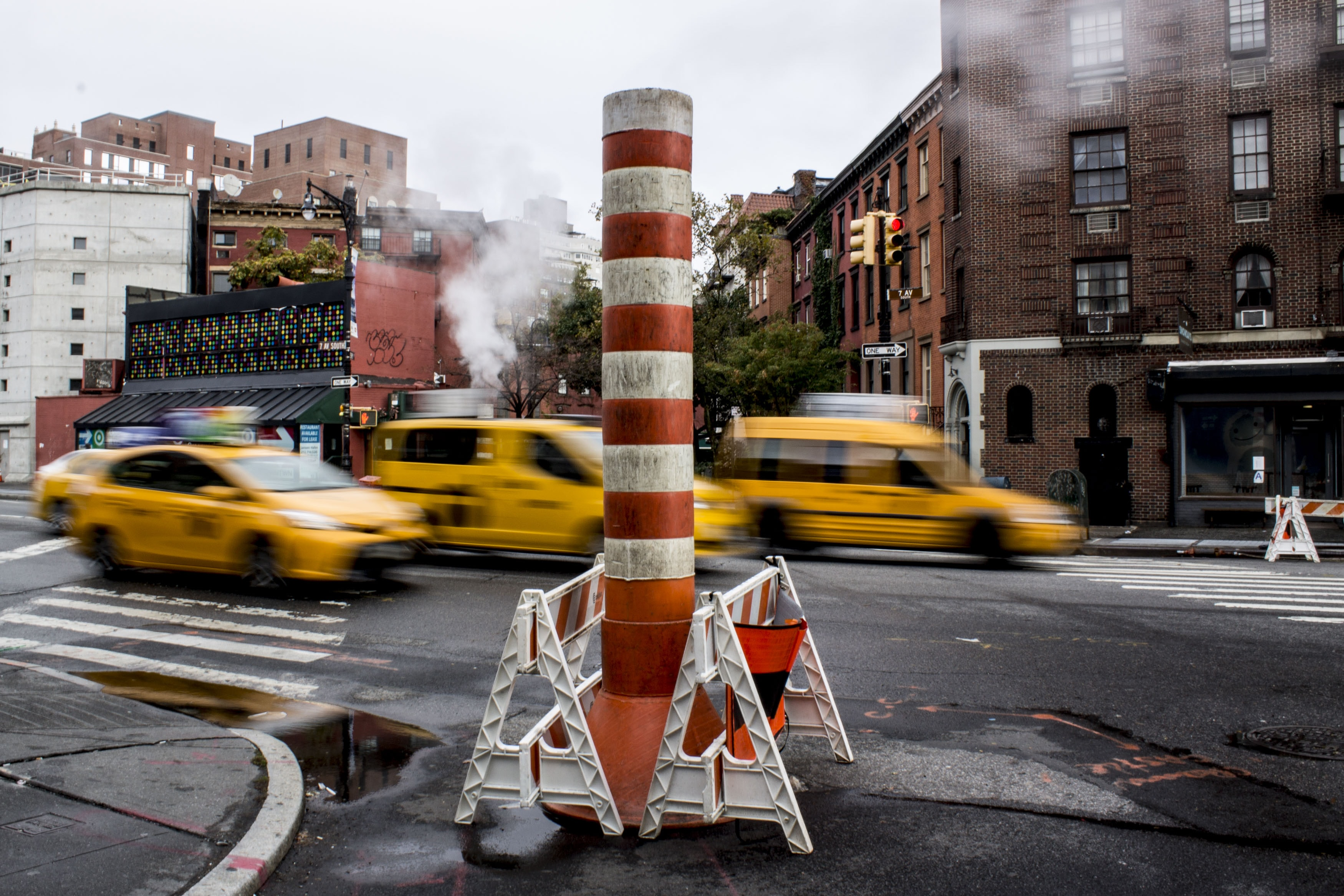 orange and white striped pole near vehicles timelapse photography