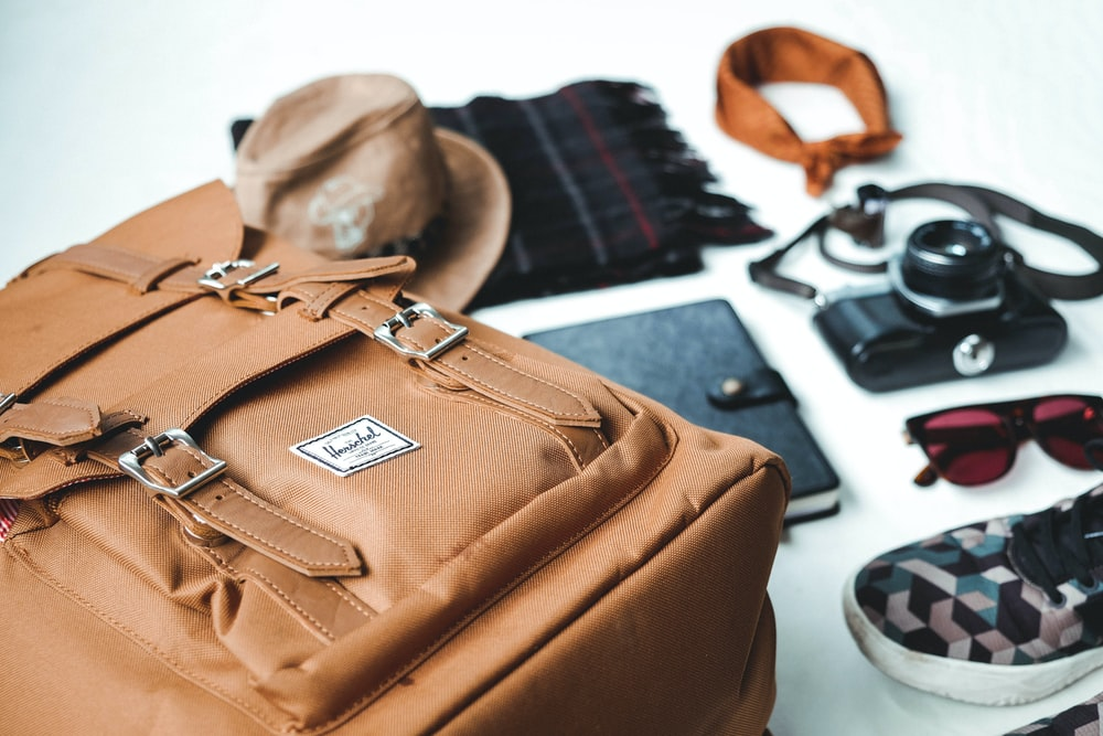 closeup photo of brown leather bag near sunglasses and shoes