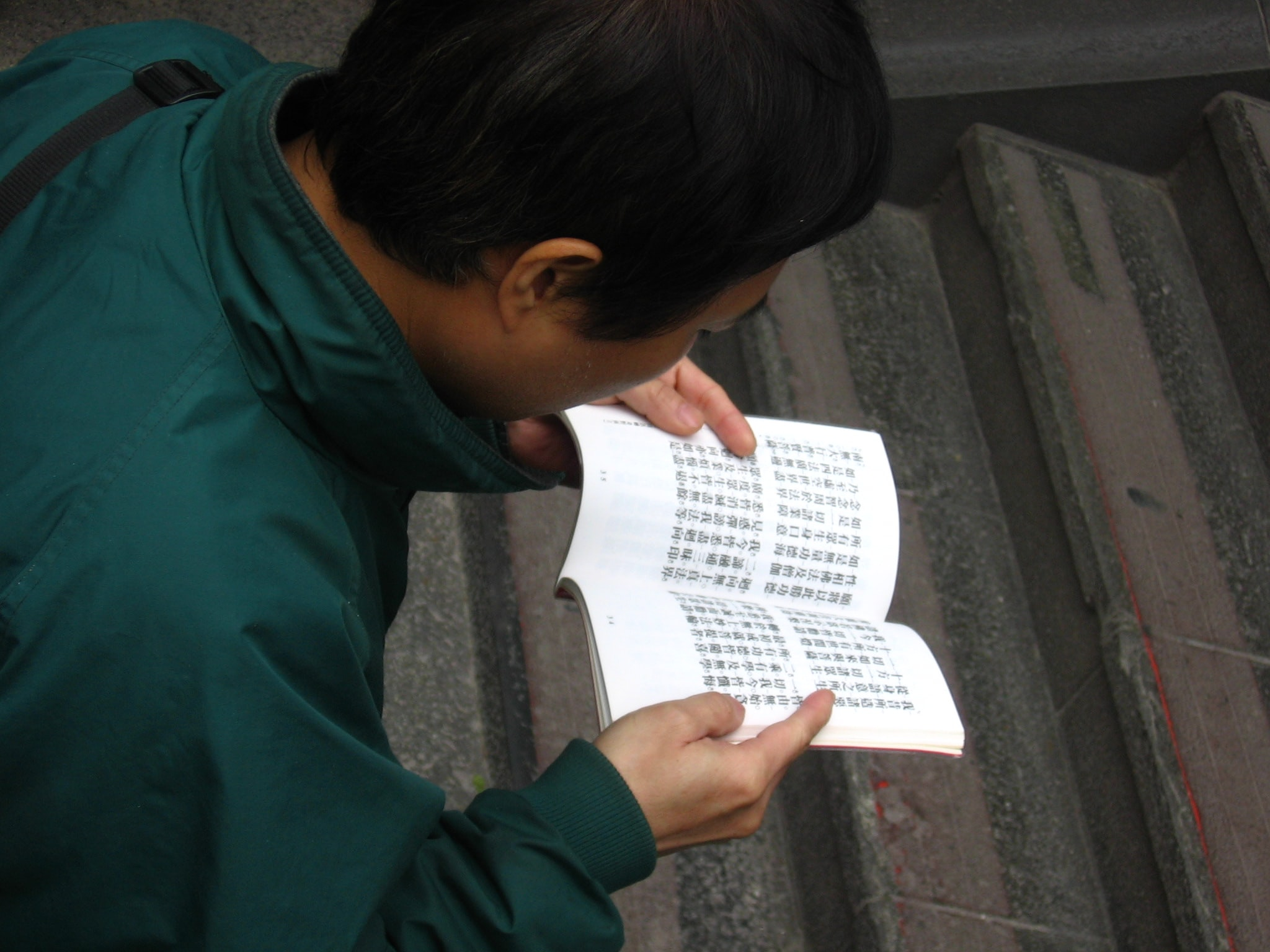 person holding white educational book