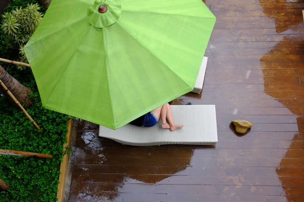 person lying on lounger under patio umbrella