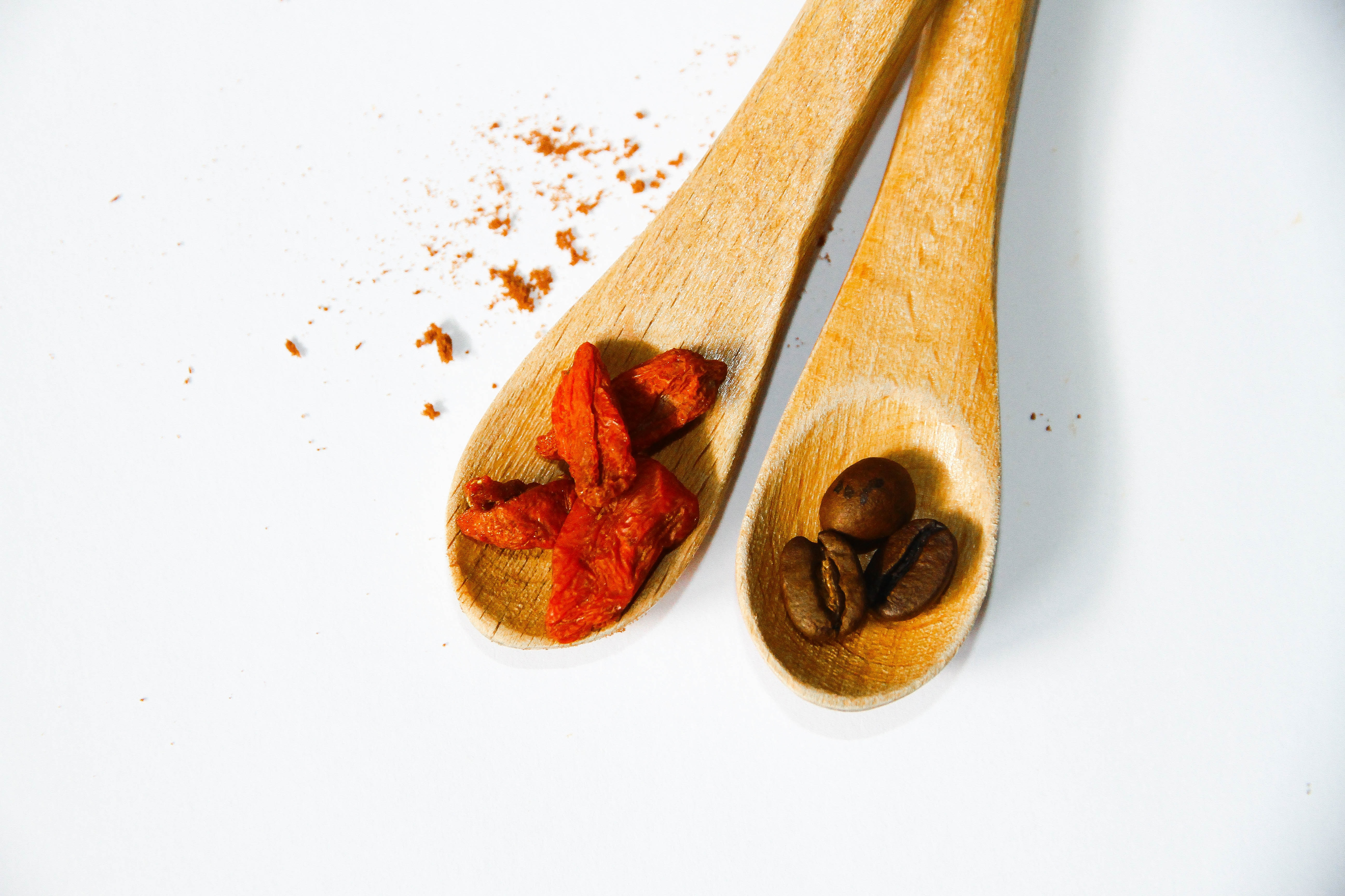 coffee beans on brown wooden spoon