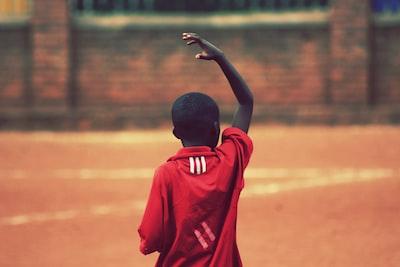 boy raising right hand above head rwanda teams background