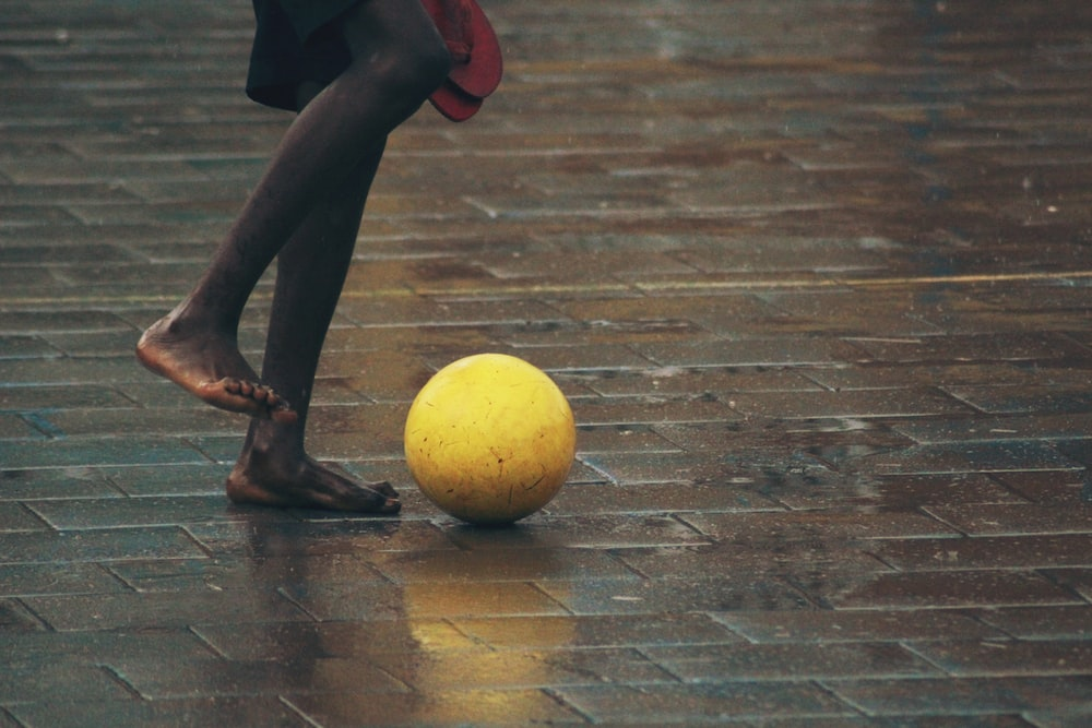 person standing gray brick floor about to kick ball