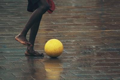 person standing gray brick floor about to kick ball rwanda zoom background