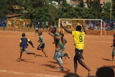 people running on soccer field during daytime rwanda teams background