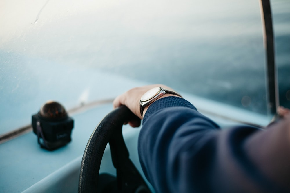shallow focus photography of person steering boat