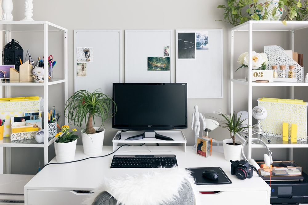 computer setup on white wooden table inside room