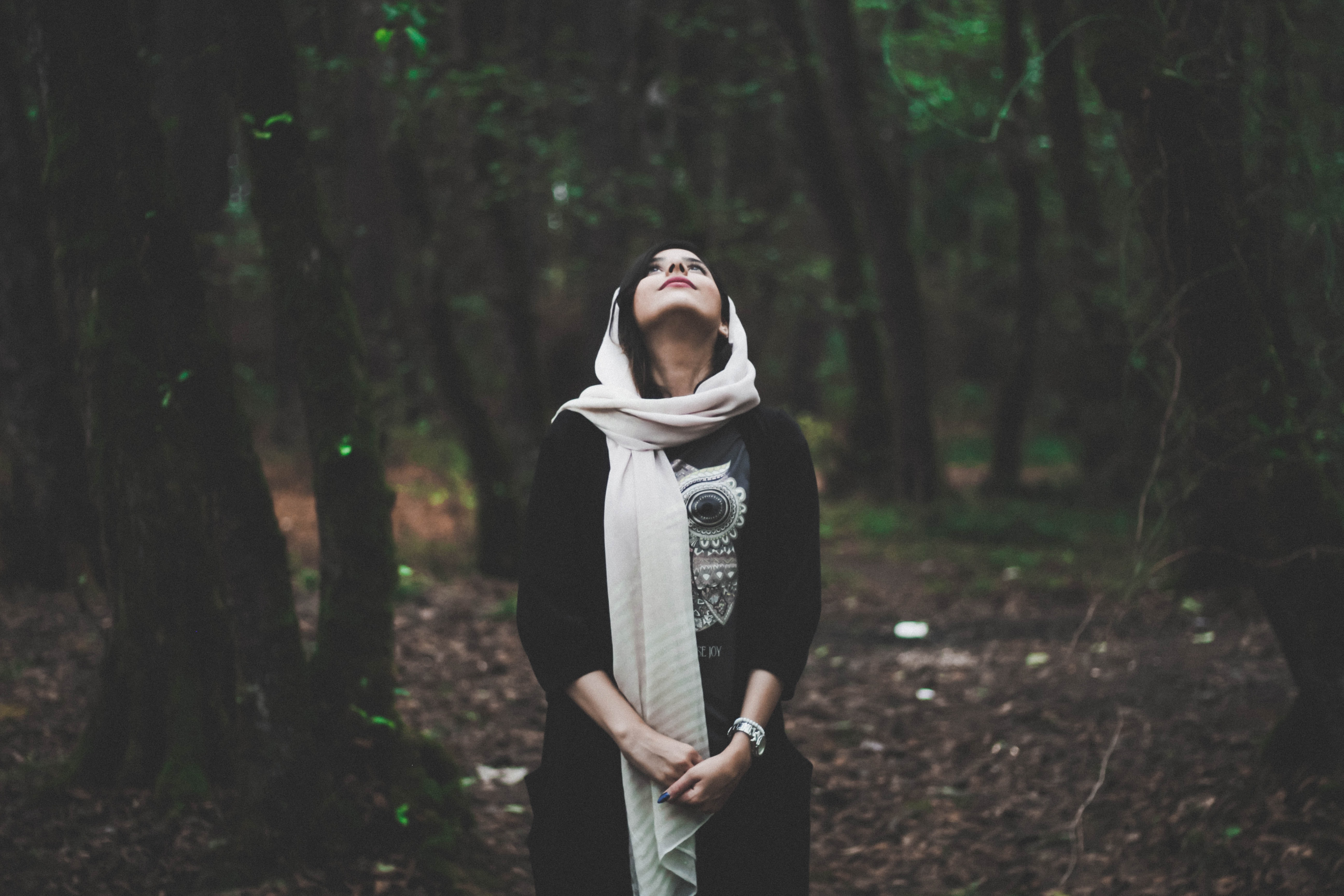 shallow focus photography of woman in forest looking upward