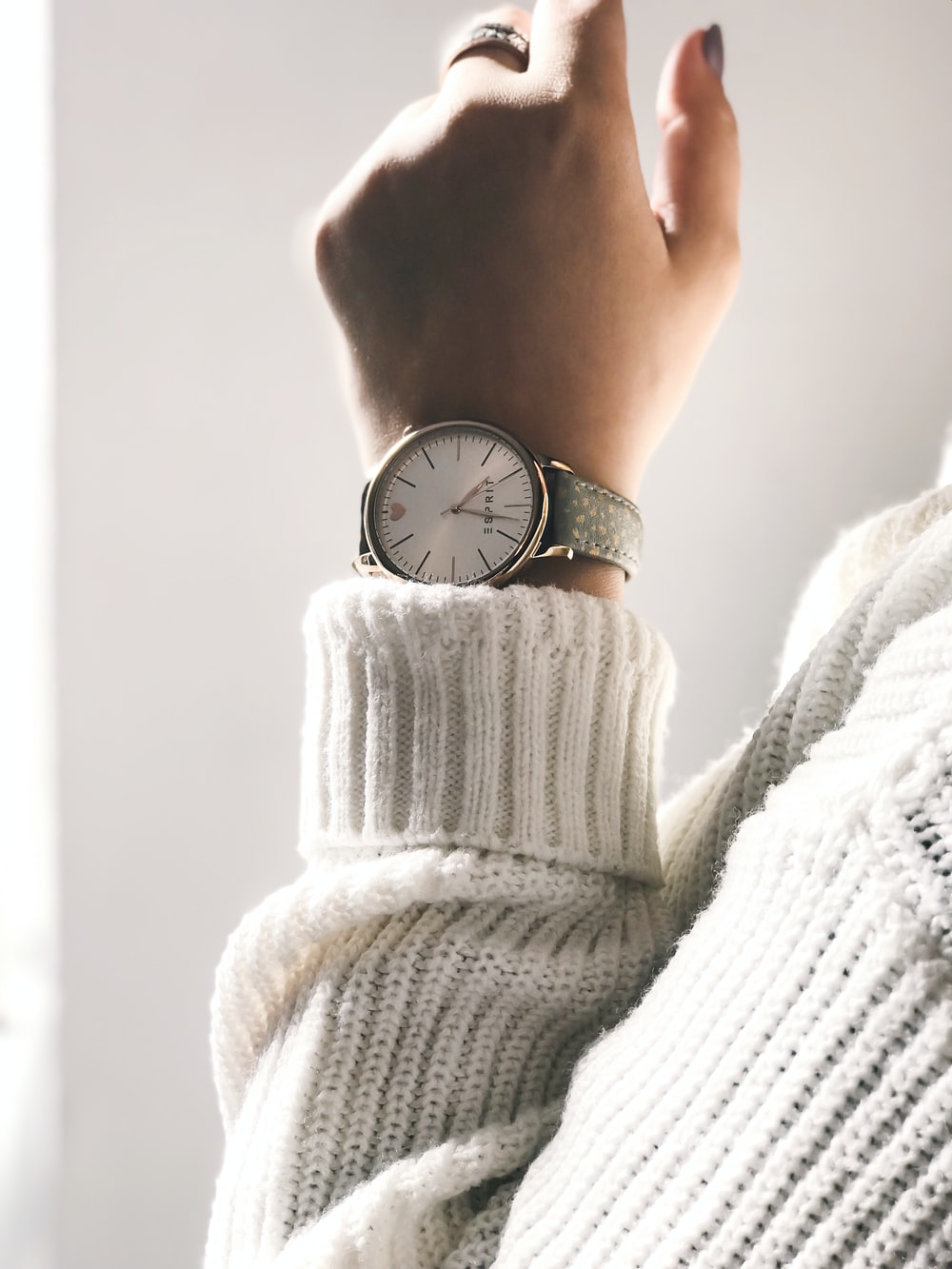 person wearing round silver-colored analog watch