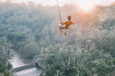 high angle photography of man sitting on swing