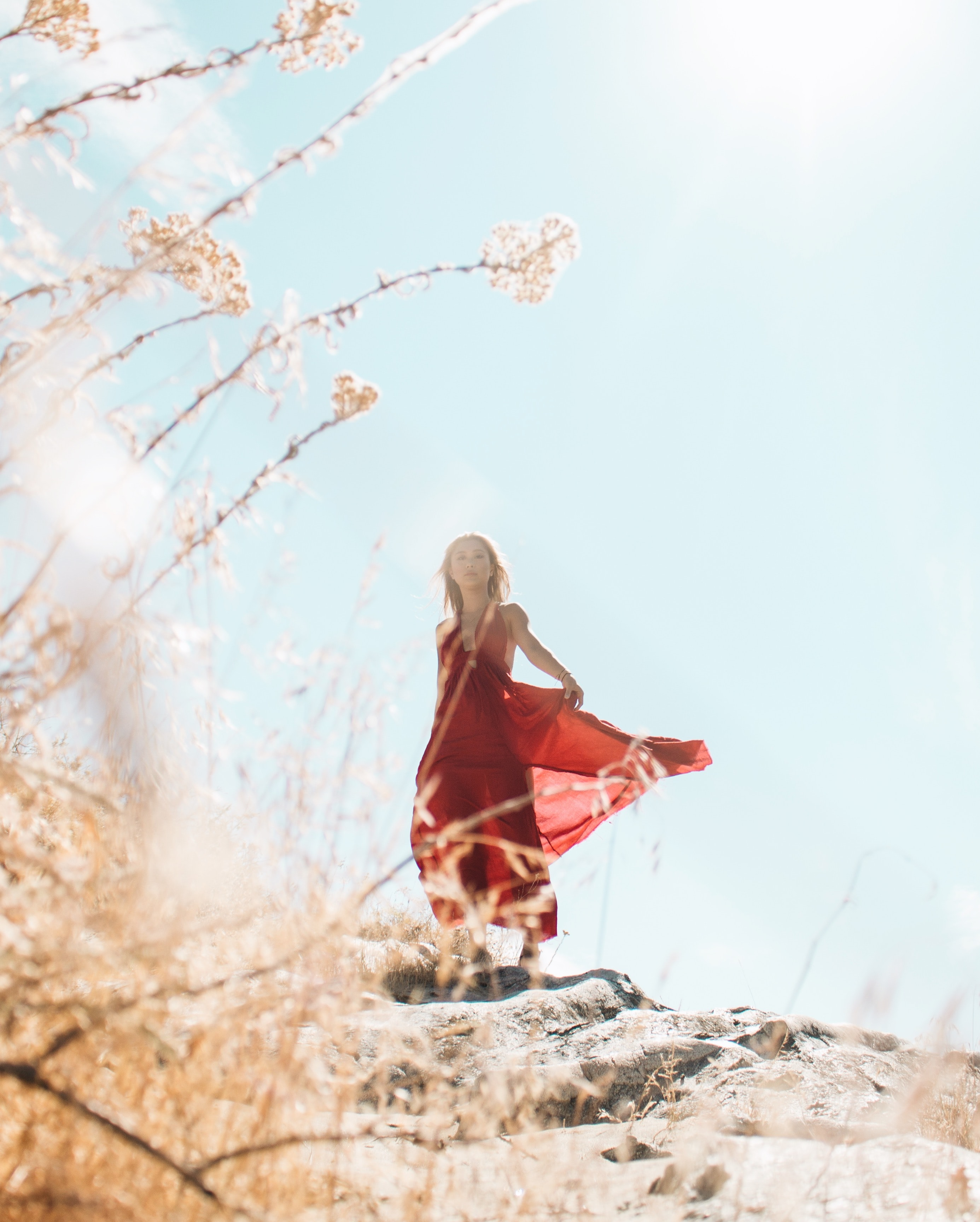 woman wearing red sleeveless dress on top of hill