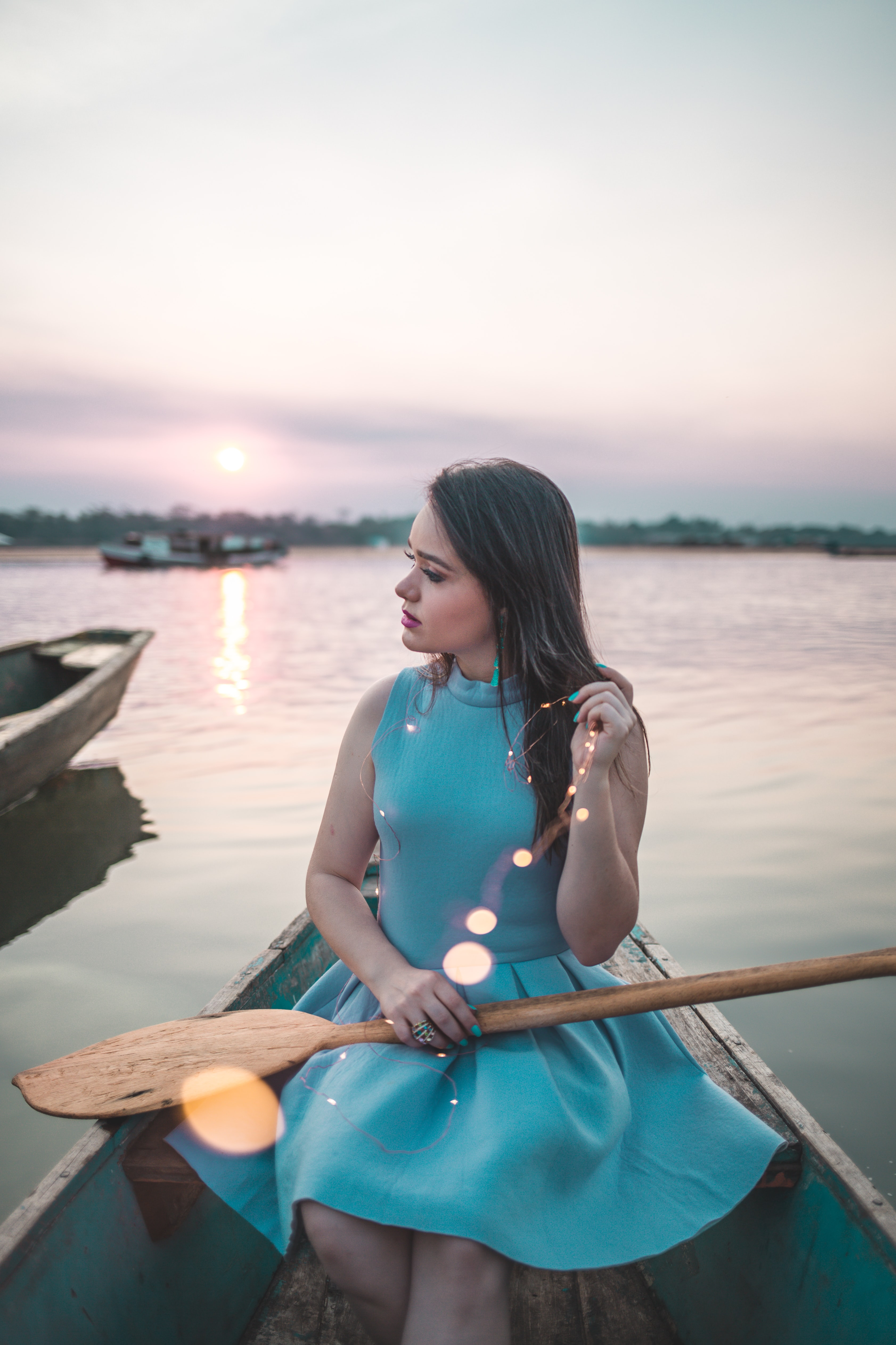 woman sitting on boat holding paddle