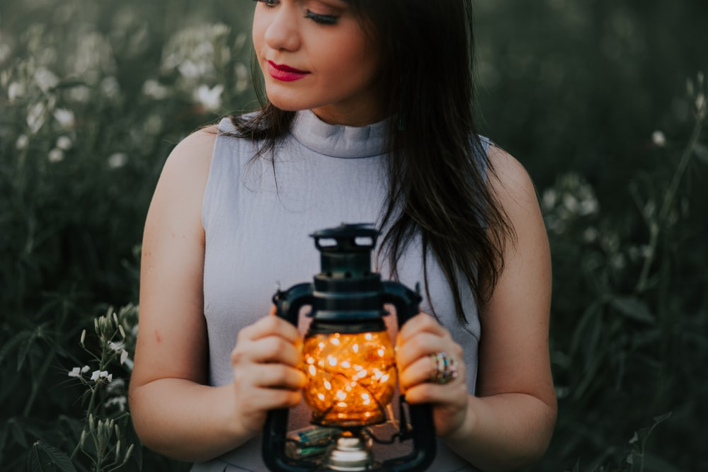 woman in gray turtle neckline top holding black camping lantern